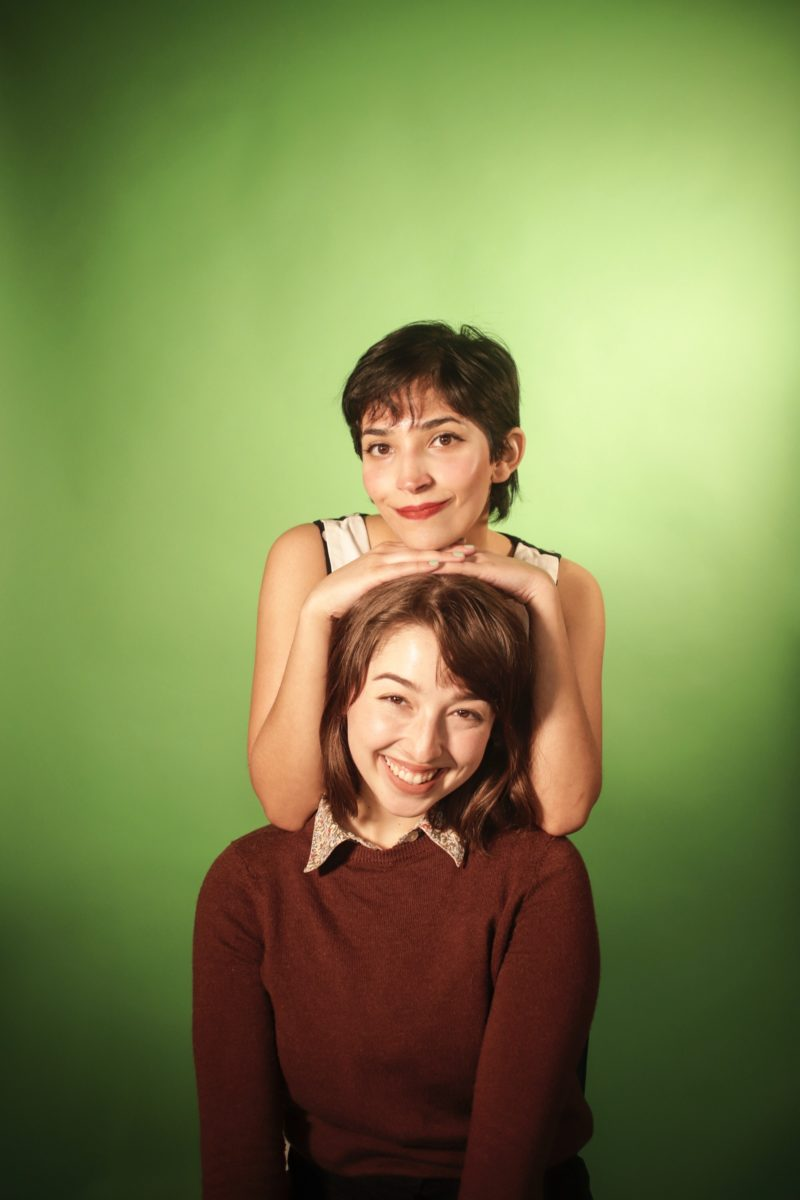 Tinu Thomas and Haley Butler pose with a green background