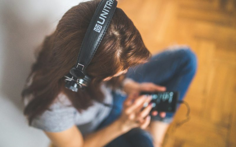 A woman wears headphones and selects something to listen to
